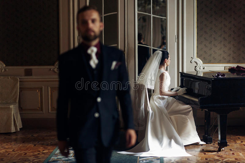 elegant gorgeous bride playing the fortepiano and stylish handsome groom posing in rich old room. sensual look. unusual luxury we royalty free stock photography