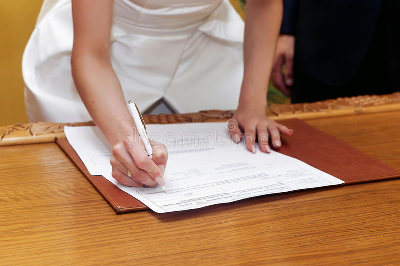 elegant gorgeous bride signing register, holding pen and official document. unusual luxury wedding couple in retro style royalty free stock photo