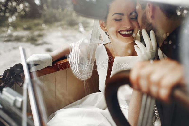 elegant gorgeous bride smiling and handsome stylish groom kissing her in car. unusual luxury wedding couple in retro style. roman royalty free stock images
