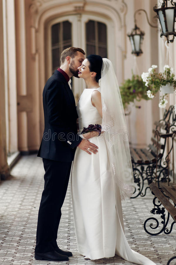elegant gorgeous bride and stylish groom hugging kissing, sensual touch on background of old building. unusual luxury wedding royalty free stock photos