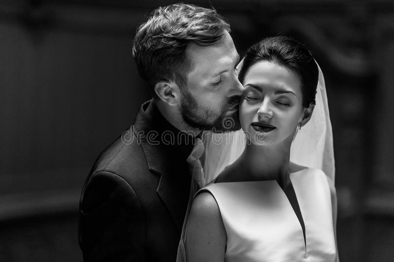 elegant gorgeous bride and stylish groom hugging, sensual touch, romantic moment. unusual luxury wedding couple in retro style. b stock photos