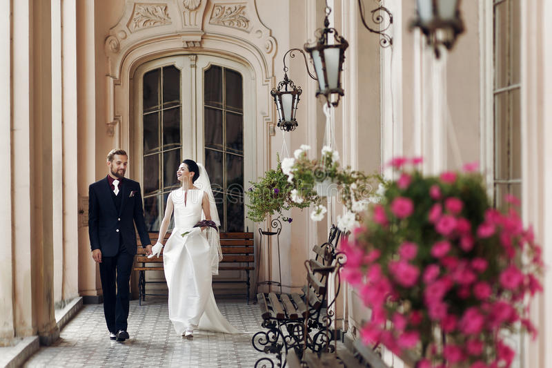 Elegant gorgeous bride and stylish groom walking holding hands,. Sensual touch on background of old building. unusual luxury wedding couple in retro style stock photos