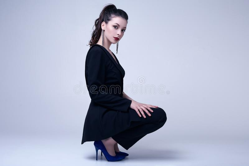Elegant gothic brunette woman with red lips in black suit royalty free stock images