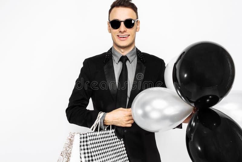 Elegant grabb i solglasögon, svart dräkt som rymmer påsar, för att shoppa royaltyfria bilder