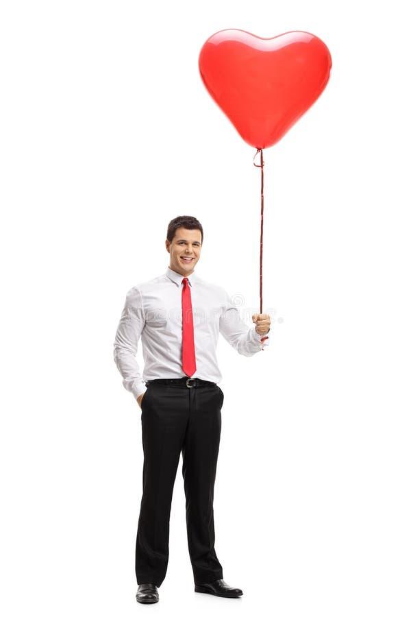 Elegant grabb som rymmer en hjärta formad ballong arkivbild