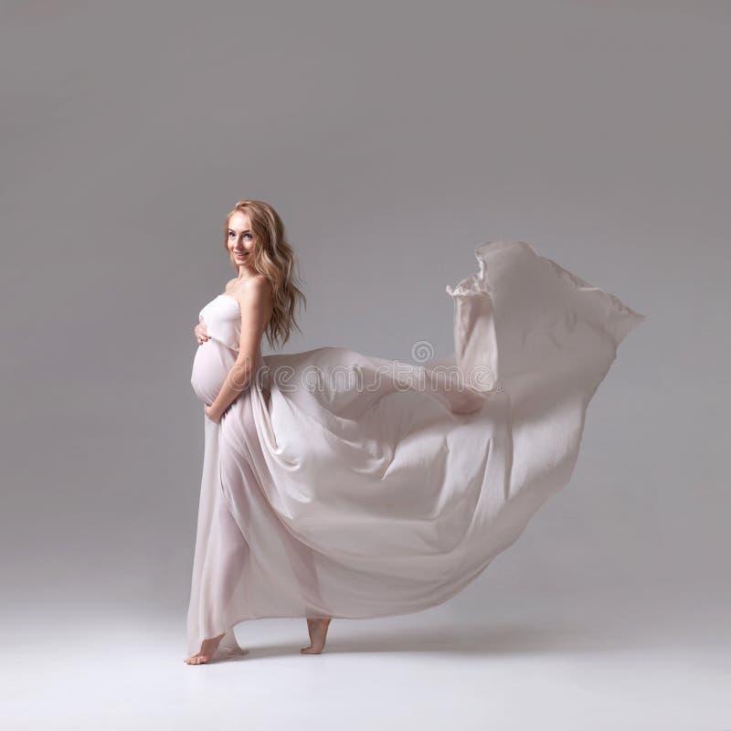 Elegant gravid kvinna i en vit flygaklänning arkivfoton