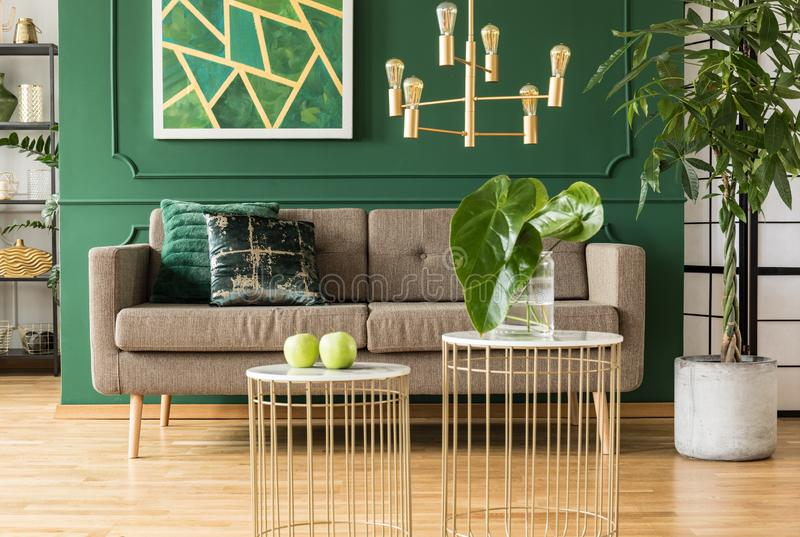 Elegant green and gold living room with brown sofa, coffee tables and golden chandelier. Elegant green and gold living room with comfortable brown sofa, coffee stock photography