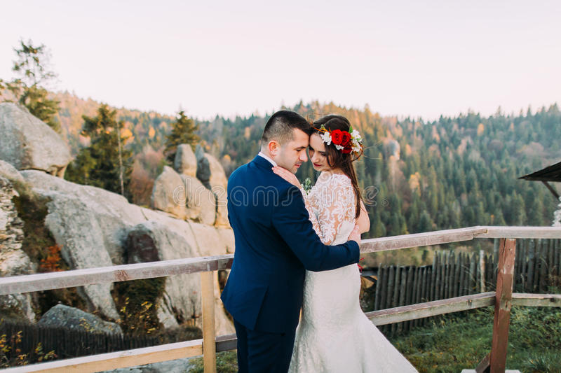 Elegant groom in stylish blue suit lovingly holding his charming white dressed bride standing on wooden platform with stock images