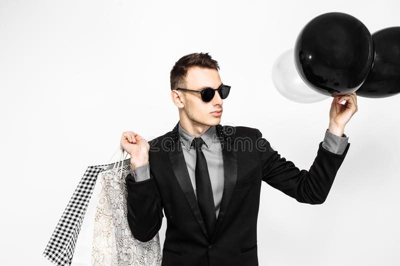 An elegant guy in a black suit and sunglasses, with shopping bag. S and balloons, is waiting for black Friday, on a white background. Black Friday, shopping stock photography