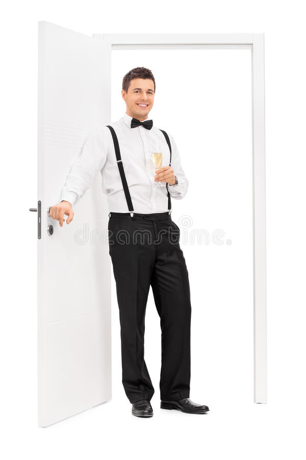 Elegant guy standing by a door and holding wine stock photo