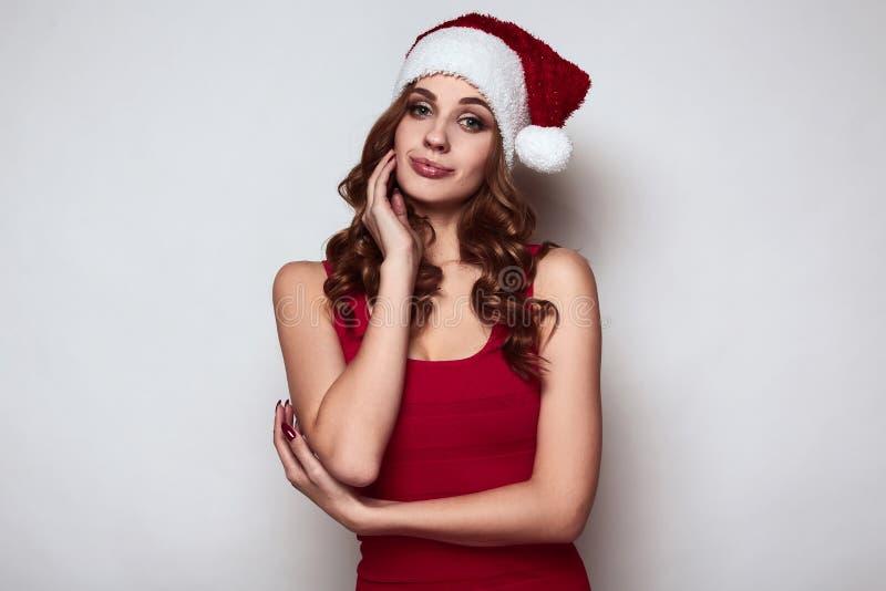 Elegant härlig kvinna i en röd klänning och julhatt royaltyfri bild