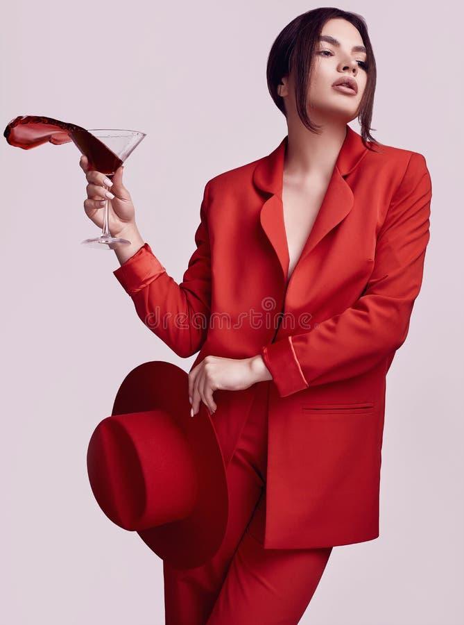 Elegant härlig kvinna i en röd trendig dräkt och hatt med coctailen royaltyfria bilder