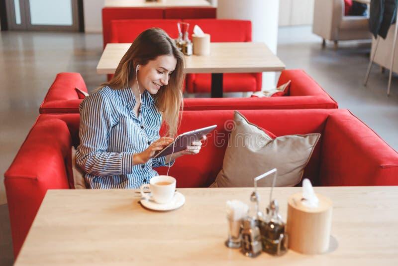 Elegant härlig kvinna med minnestavladatoren som dricker te på kafét arkivfoto