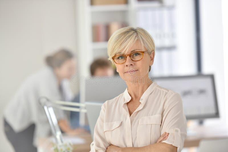 Elegant hög affärskvinna på kontoret arkivbild