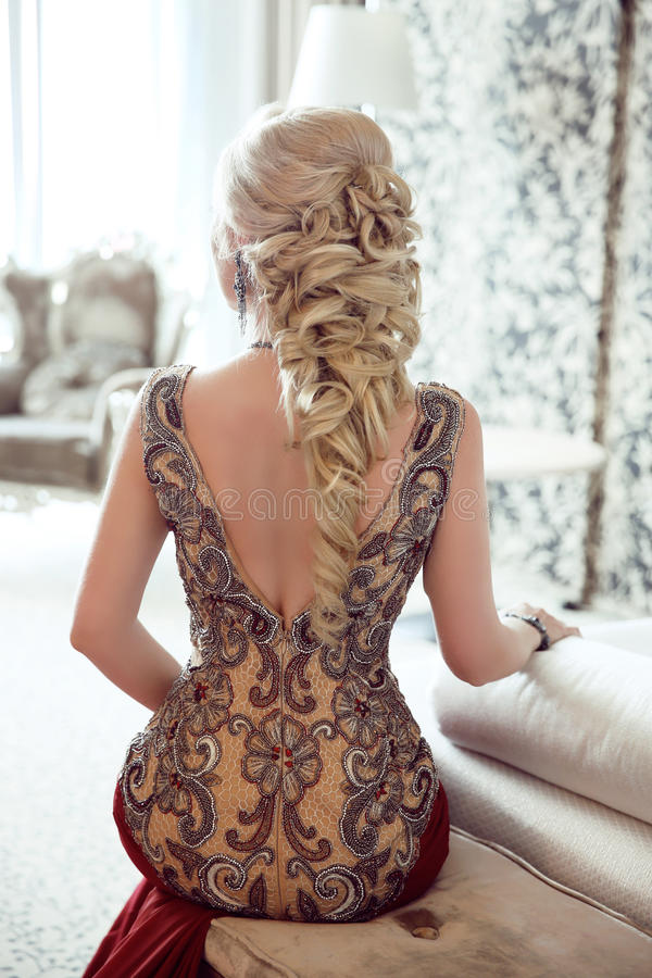 Elegant hairstyle. Beautiful blond woman in fashion red dress si stock photography