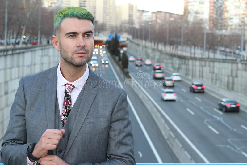 Elegant handsome man with green hair in the city royalty free stock images