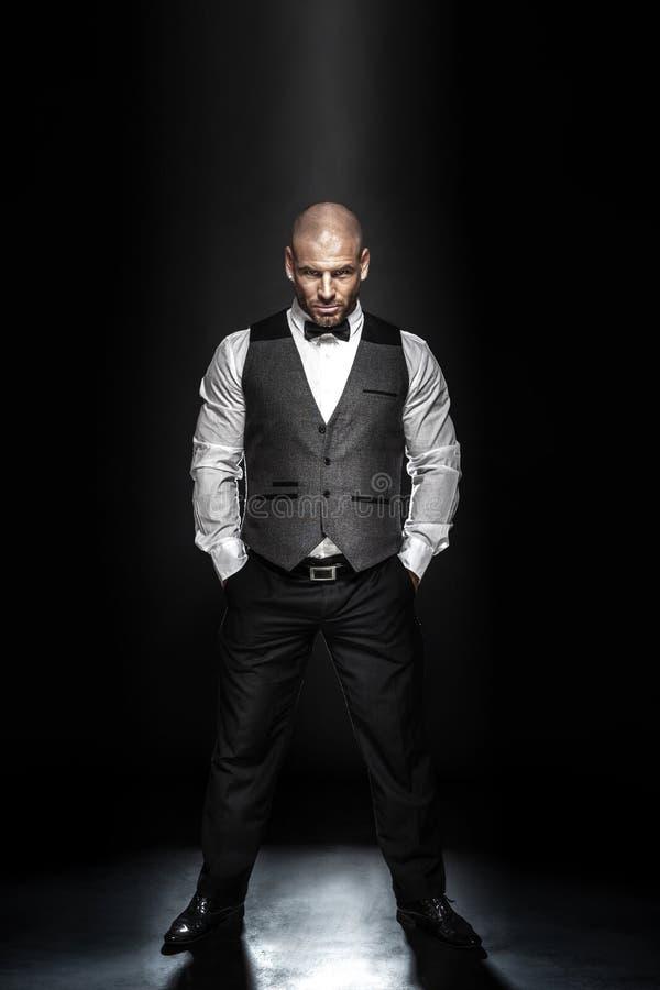Elegant handsome man posing. Fashion shot of an elegant young man wearing suit on black background stock photography