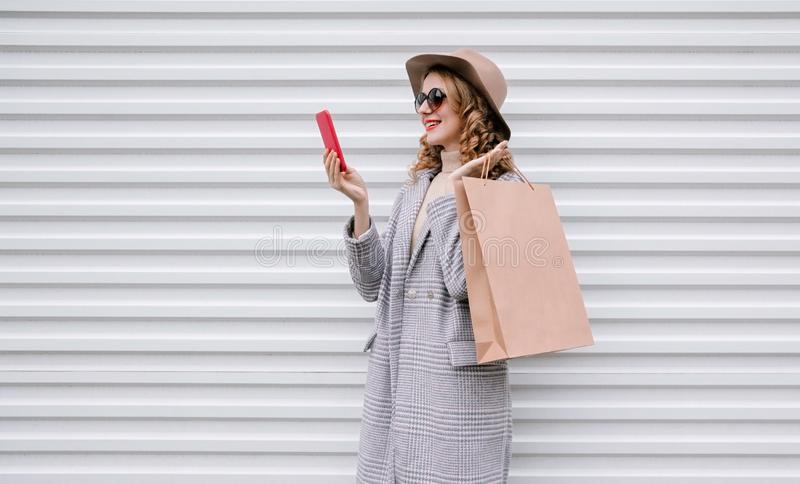 Elegant happy smiling woman holding phone with shopping bag in gray coat, round hat on city street over white wall stock image