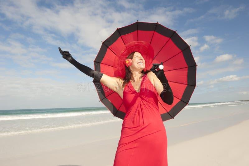 Elegant happy woman red dress beach