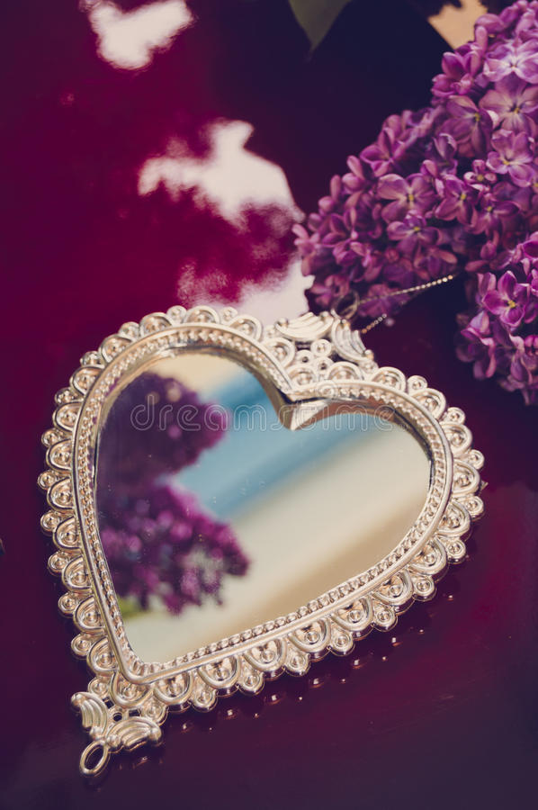 Elegant heart-shaped mirror and lilac royalty free stock image