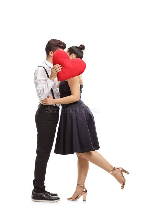 Elegant het geklede paar kussen achter een hart royalty-vrije stock afbeeldingen