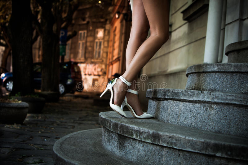 Elegant high heel shoes. Woman legs on stairs in elegant white high heel shoes outdoor shot summer day stock photo
