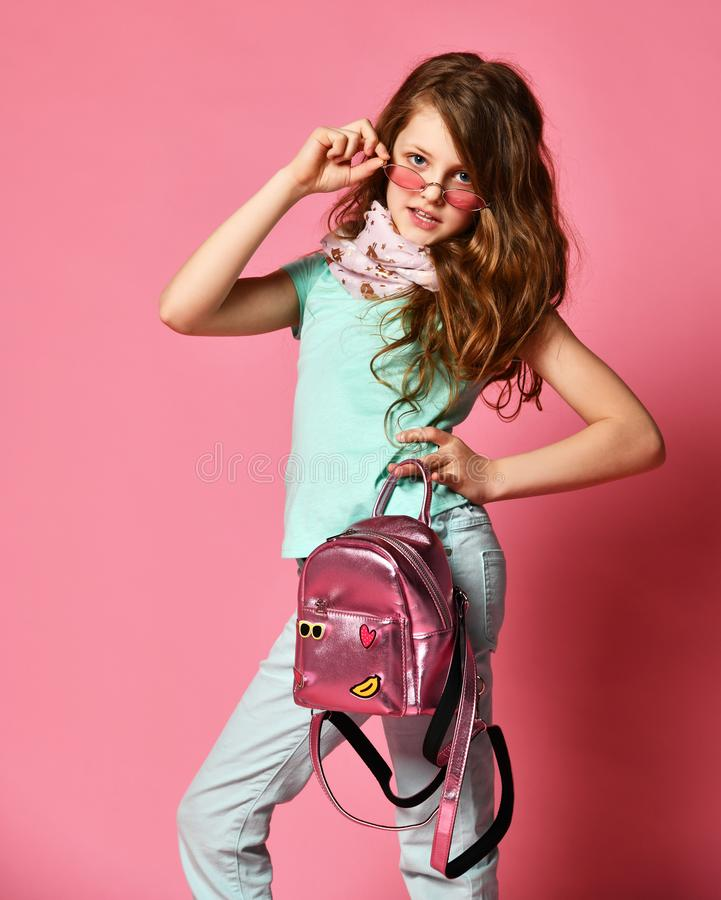 Elegant high society girl teen in fashion scarf and with shiny backpack looks at us inquiringly over her modern sunglasses royalty free stock images