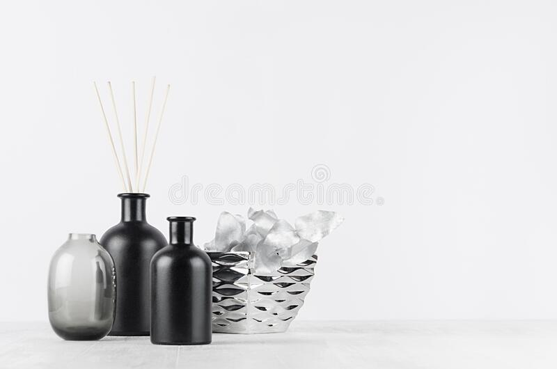 Elegant home decor with glass black diffuser bottles, silver branch, decorative bowl on  white wood table, wall. Elegant home decor with glass black diffuser stock images