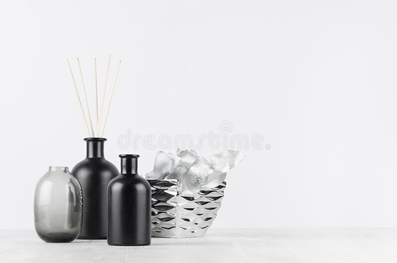 Elegant home decor with glass black diffuser bottles, silver branch, decorative bowl on white wood table, wall. Elegant home decor with glass black diffuser stock photos