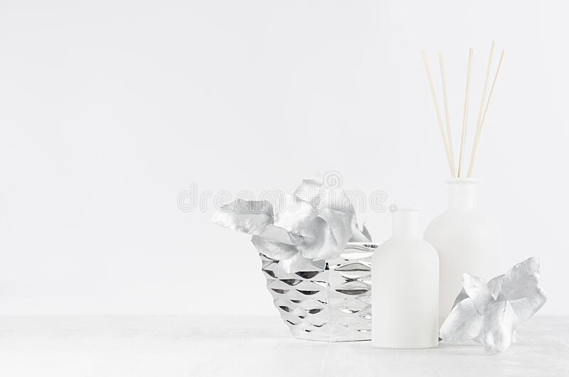 Elegant home decor with glass white aroma diffuser bottles, sticks, silver branch, bowl on white wood table, wall. Elegant home decor with glass white aroma royalty free stock photography