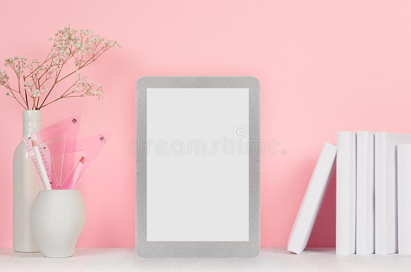 Elegant home workplace with stylish silver blank tablet and white stationery, flowers in vase on pink background. stock photos