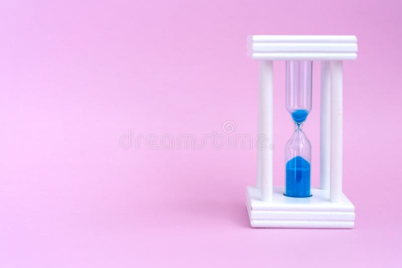 Elegant hourglass with running blue sand on pink backgroun stock photo