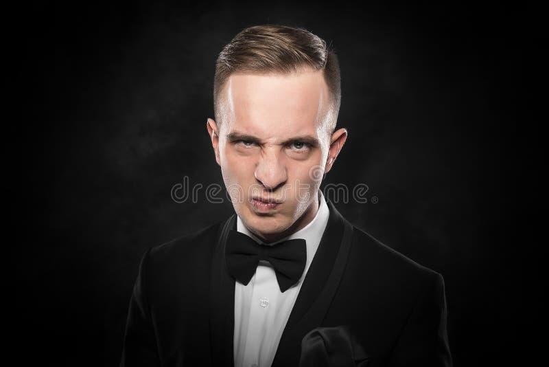 Elegant ilsken ung man i dräkten som ser rynka pannan royaltyfri bild
