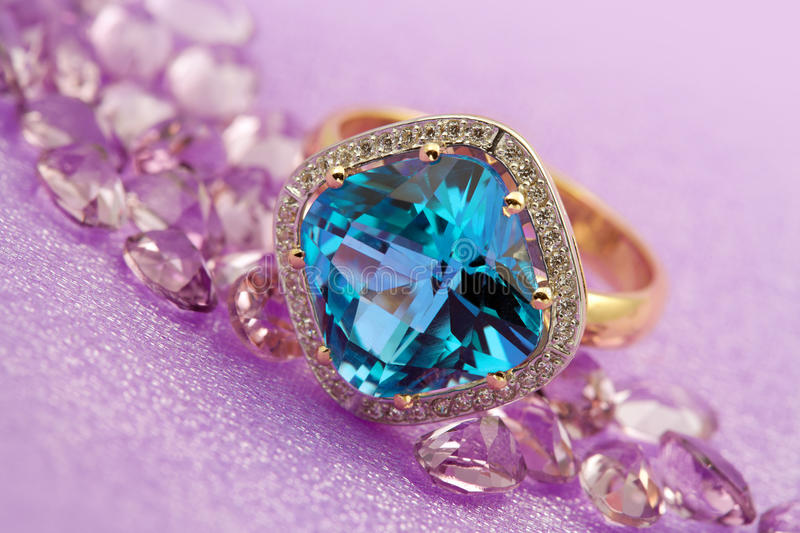 Elegant jewelry. Ring with blue topaz and jewel stone - amethysts royalty free stock photography