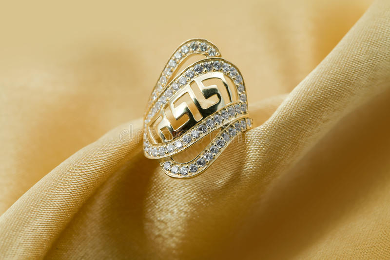 Elegant jewelry ring. With jewel stone - brilliants on a background of golden silk stock image