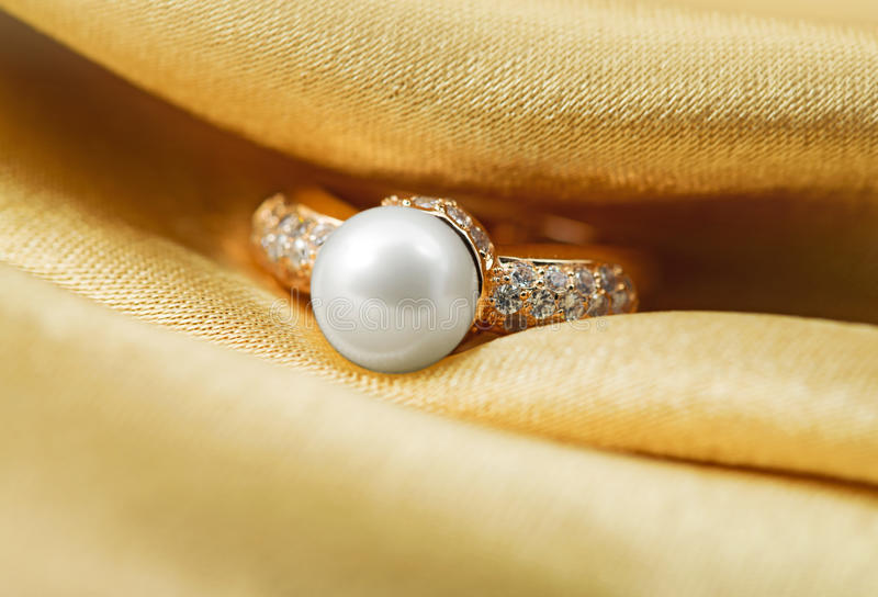 Elegant jewelry ring with pearl and brilliants. Elegant jewelry ring with jewel stone on a background of golden silk royalty free stock photos