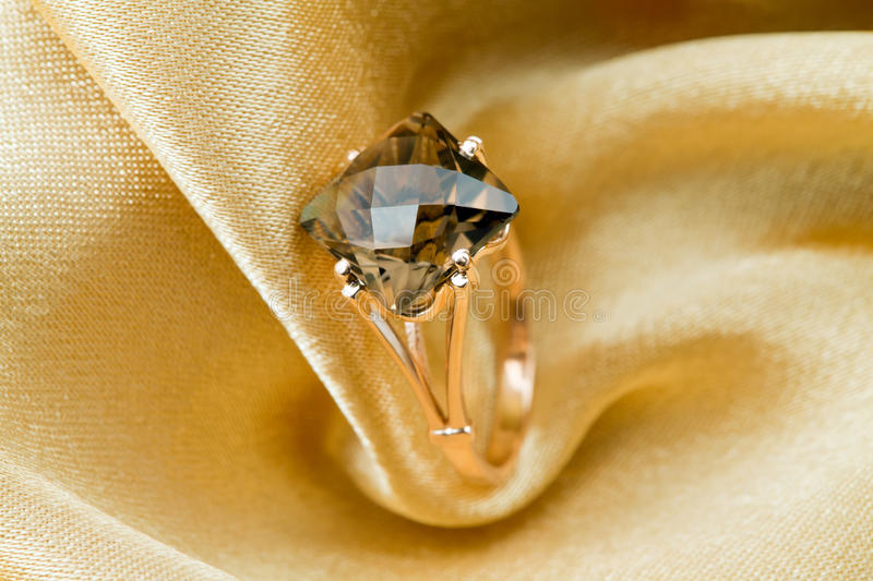 Elegant jewelry ring with topaz. Elegant jewelry ring with jewel stone on a background of golden silk royalty free stock photos