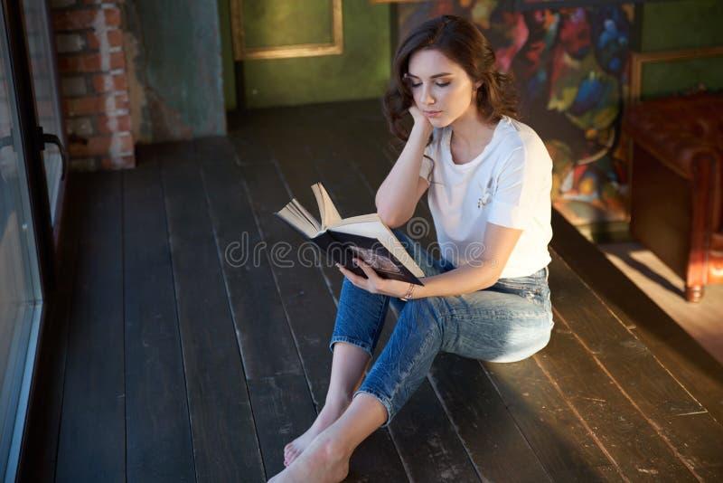 Elegant jong donkerbruin meisje die een boekzitting op de vloer in de ruimte lezen Modieuze binnenlandse en zonglans, comfortabel stock fotografie