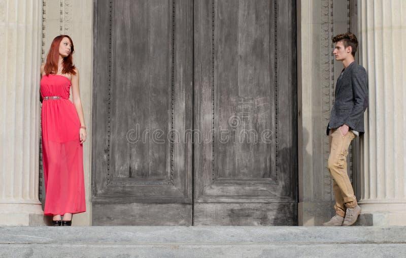 Elegant jong paar dat door grote houten deur wordt gescheiden stock foto's