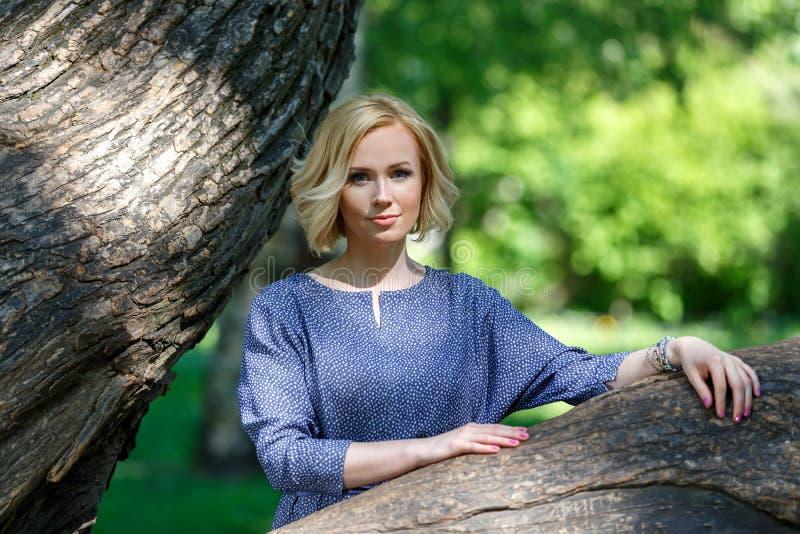 Elegant jong vrouwelijk model die op grote linde in het park leunen royalty-vrije stock fotografie