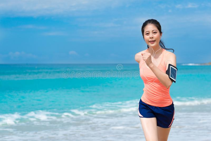 Elegant jong wijfje die jogger op strand lopen stock foto
