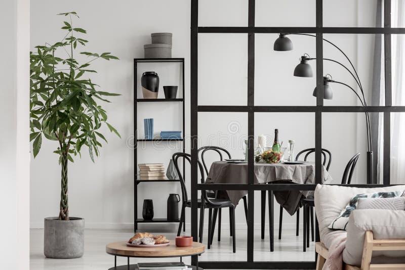 Elegant keuken en eetkamerbinnenland met zwart-wit ontwerp en installatie in concrete pot stock foto