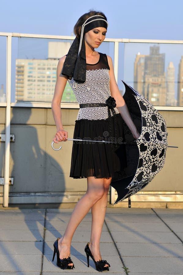 Elegant kläder för formgivare för modemodell bärande och innehavparaply arkivfoton
