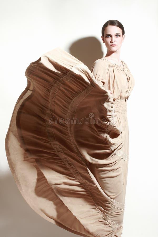 Elegant kvinna i flygklänning guld- modell för klänningmode royaltyfri bild