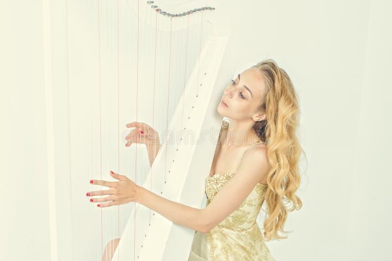 Elegant kvinna i guld- klänning med långt blont hår som spelar harpan, på vit bakgrund royaltyfria bilder