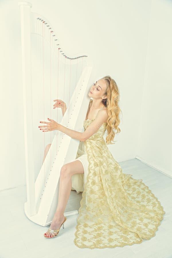 Elegant kvinna i guld- klänning med långt blont hår som spelar harpan, på vit bakgrund royaltyfri fotografi