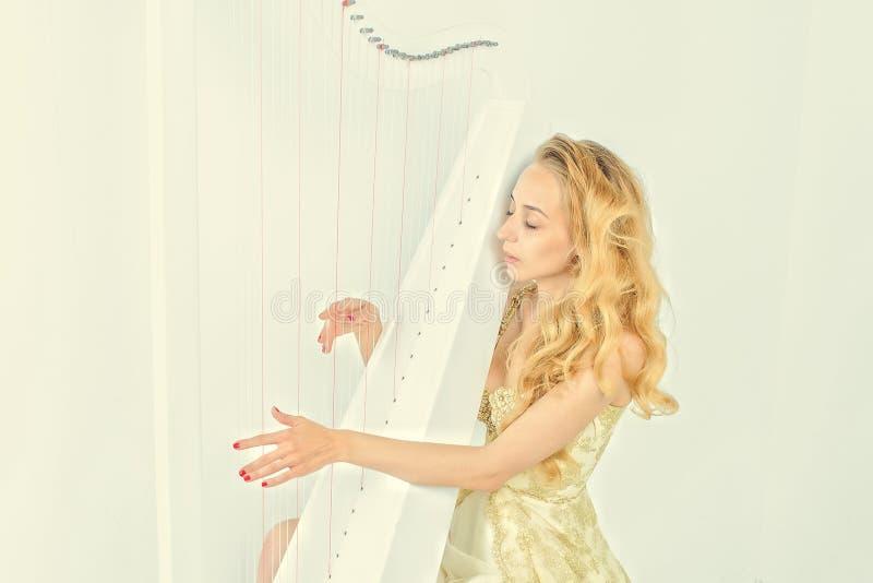 Elegant kvinna i guld- klänning med långt blont hår som spelar harpan, på vit bakgrund royaltyfri foto
