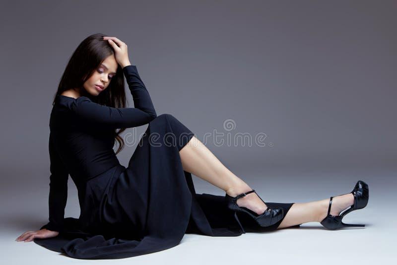 Elegant kvinna i lång svart klänning royaltyfri foto