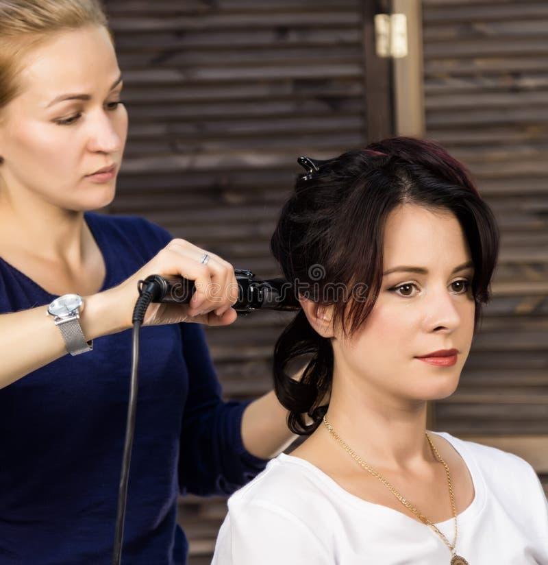 Elegant kvinna i skönhetsalong Frisören gör frisyr i form av stor krullning Begreppsbröllopfrisyr arkivbilder