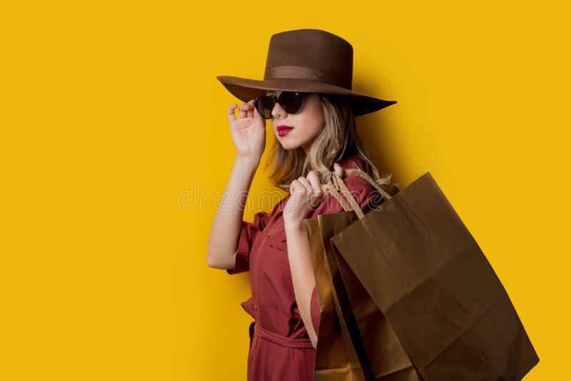 Elegant kvinna i solglasögon och med shoppingpåsar royaltyfri bild